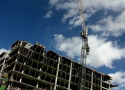 stock-footage-time-lapse-crane-swings-across-cloud-filled-sky-over-building-construction-site-p